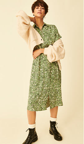 Woman wearing green printed dress with cream cardigan and black boots