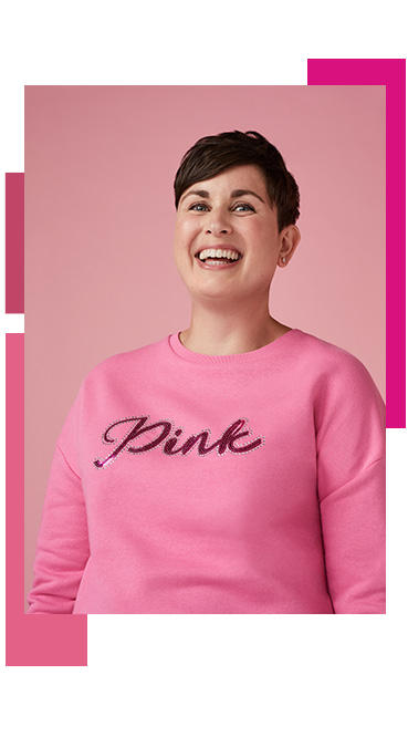 Woman laughing wearing a pink jumper spelling 'Pink'