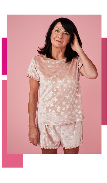 Woman wearing a pink pyjama set designed with stars