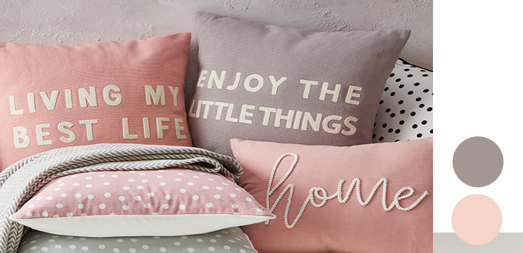 An assortment of slogan and polka dot cushions in pink, white and grey