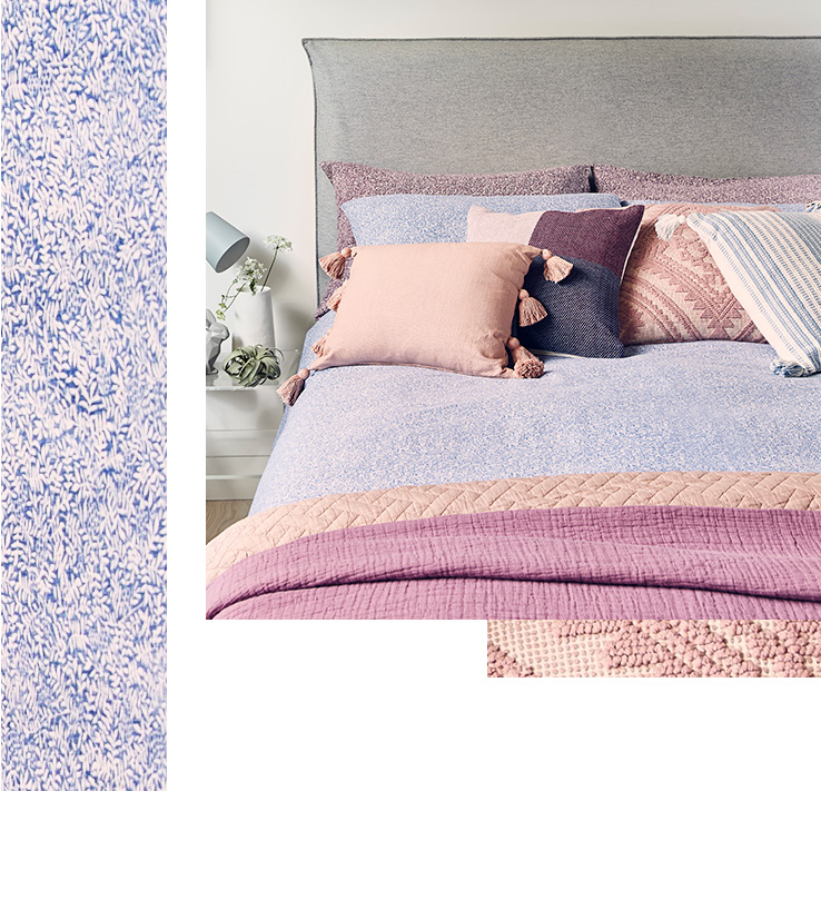 A double bed with blue printed bedding, an assortment of pink patterned cushions and matching throw