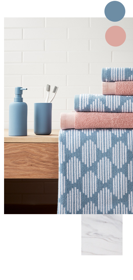 A matt blue dispenser and tumbler beside patterned blue and pink towels