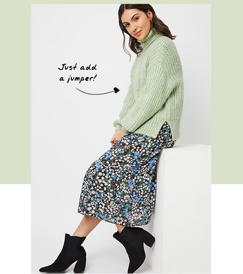 Woman wearing a floral dress with a green jumper over the top