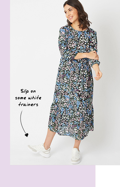 Woman wearing a floral dress and white trainers