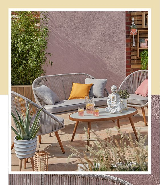 A patio with a Nerja 4 piece outdoor sofa set with cushions and ornaments