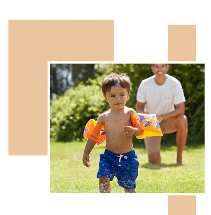 Child wearing orange armbands and navy swimming trunks running through water spray while his dad watches on