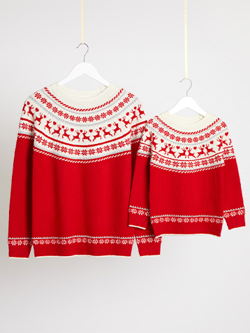 Matching adult and child red Christmas jumpers on hangers hanging from string