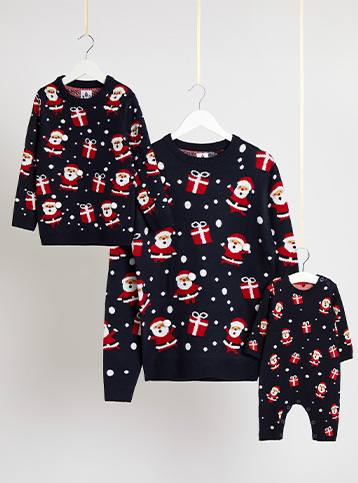 Matching adult and child navy Christmas jumpers and a baby all in one on hangers hanging from string