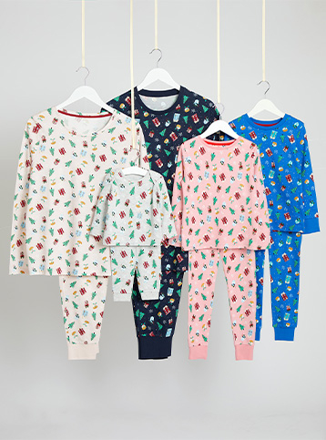 Grey, navy, pink and blue matching pyjamas with Christmas icons, all on hangers hanging from string