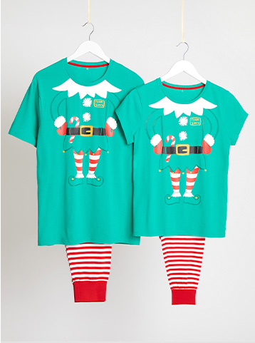 Adult and child matching green pyjamas with an elf design on hangers hanging from string