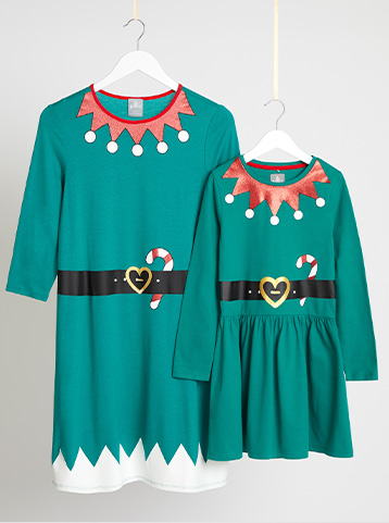 Adult and child matching Christmas elf dresses on hangers hanging from string
