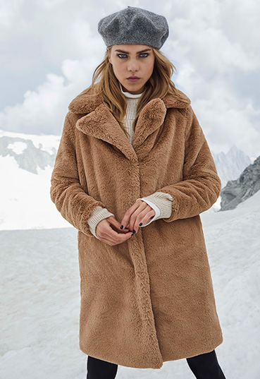 Woman in brown borg coat and grey hat on a mountainside