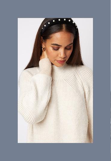 Woman in cream rib knit high neck longline jumper
