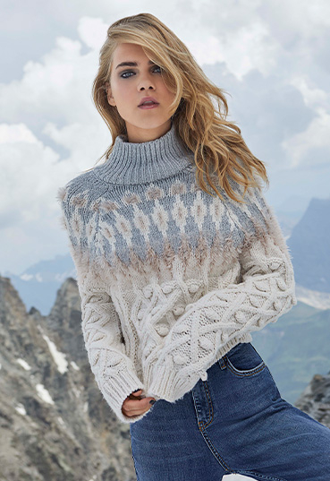 Woman posing on mountainside in oatmeal cable knit Fair Isle jumper