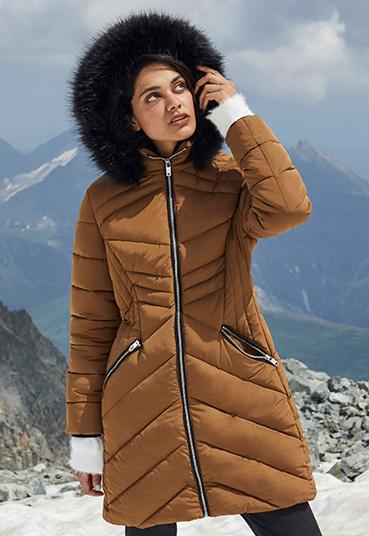 Woman in bronze faux fur hood longline padded coat on mountainside