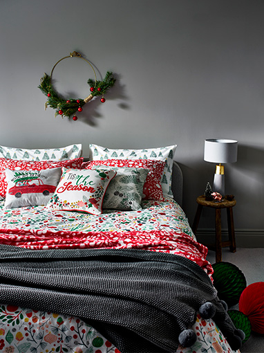 Floral Christmas bedding with cushions, a red throw and grey throw
