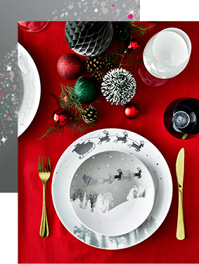Bird's-eye view of table with red tablecloth, festive crockery, gold cutlery and red and green ornaments