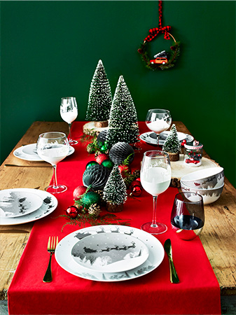 Table with red tablecloth, festive crockery, gold cutlery and red and green ornaments