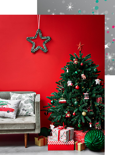 Christmas tree with presents next to a sofa