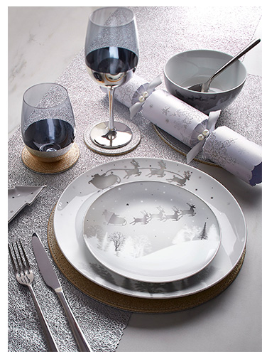 White Christmas dinnerware on a table surrounded by silver glassware and cutlery