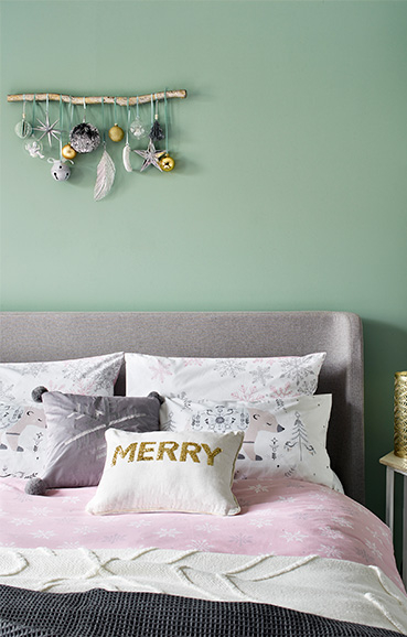 Pink snowflake bedding with matching pillows and Christmas cushions with a white and grey throw