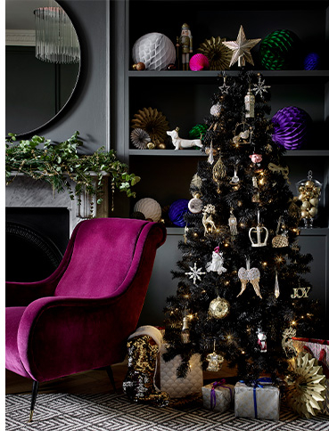 Christmas tree decorated with golden baubles and ornaments with presents underneath