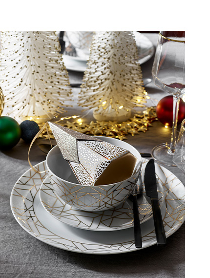 Gold and crockery on a table next to gold and white Christmas tree ornaments