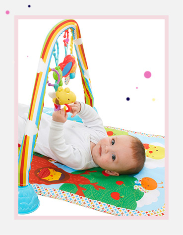 A baby with a Vtech Little Friendlies Glow & Giggle Playmat