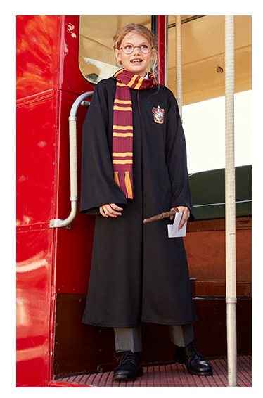 A girl wears Gryffindor Hogwarts robes