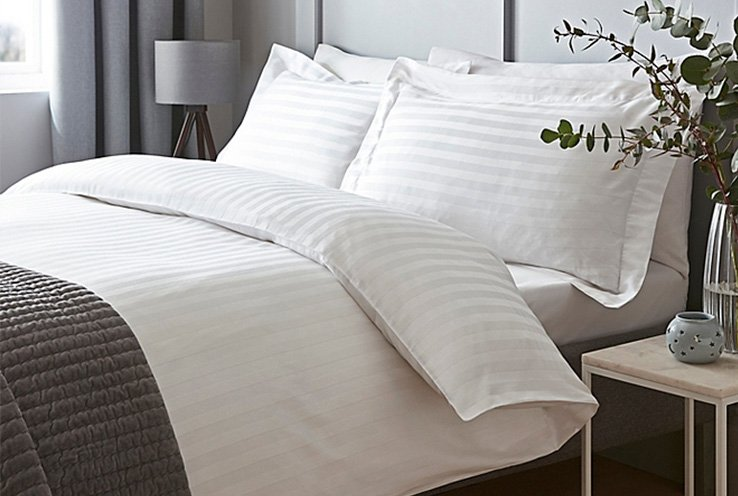 Double bed in white subtle stripe bedsheets and pillowcases