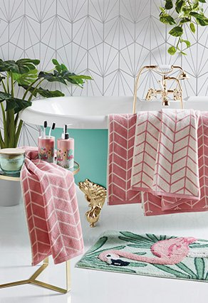 Decorated bathroom with green bathtub with pink towels rapped over the sides and a flamingo bath matt