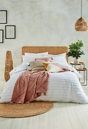Double bed in white bedsheets with soft pink blanket and pillows over the top