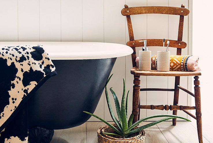 Navy bathtub next to a wooden chair with soap dispenser and towels on