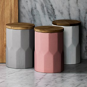 Three storage containers in dark grey, pink and light grey
