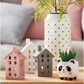 Home ornaments with three small standing houses in pink, white and grey. Small panda plant pot and white polka dot vase with plat inside