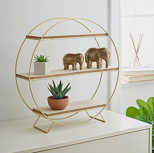 Gold standing circle decoration with shelves with gold elephant ornaments with a white and brown plant pot sitting on the shelves