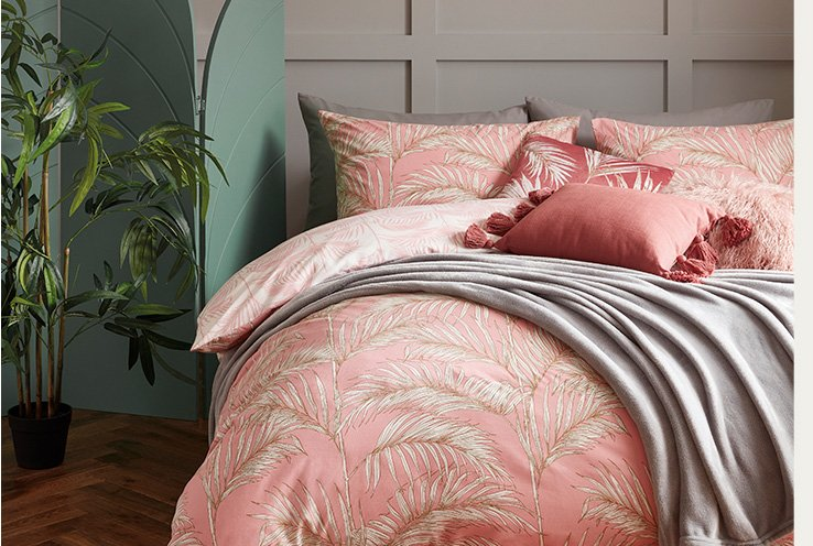 Double bed with pink retro floral duvet set, matching cushions and a grey throw