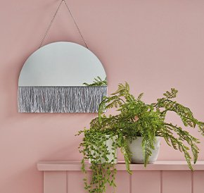 A semi-circle mirror with grey fringing and an artificial plant