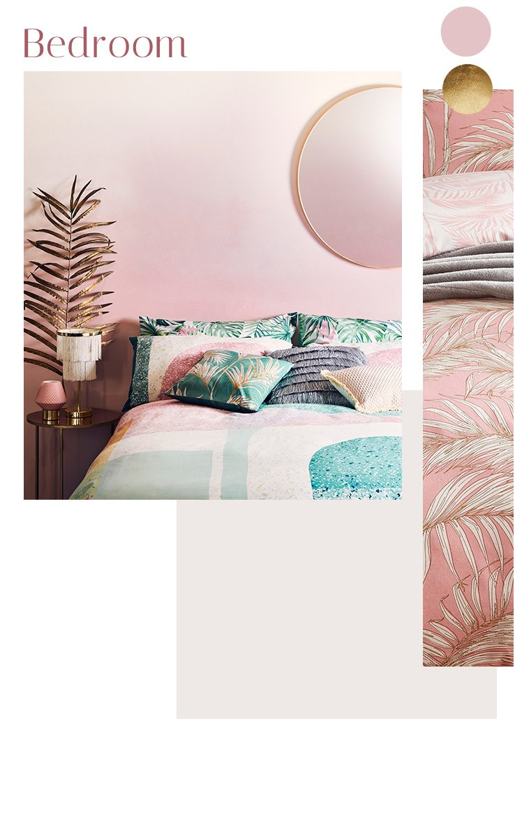 A bedroom with a large circular mirror on a pink wall, a double bed with geometric bedding and an assortment of cushions, and table lamps on a gold side table