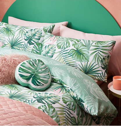 A double bed with a green paradise palm leaves print duvet set, a matching cushion, a pink faux fur cushion and a pink throw