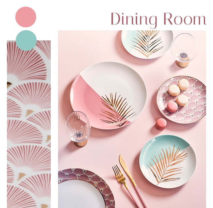 A pink table with glassware, gold-tone cutlery and tableware designed with gold-tone palm leaves