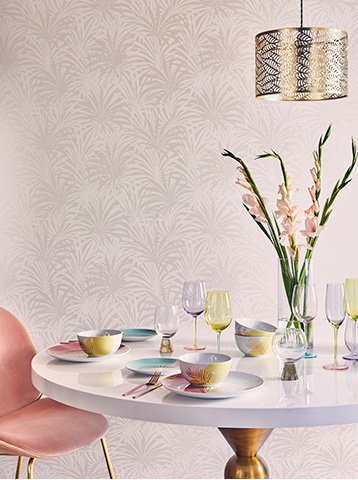 A table with a range of colourful plates and glasses, and an artificial plant