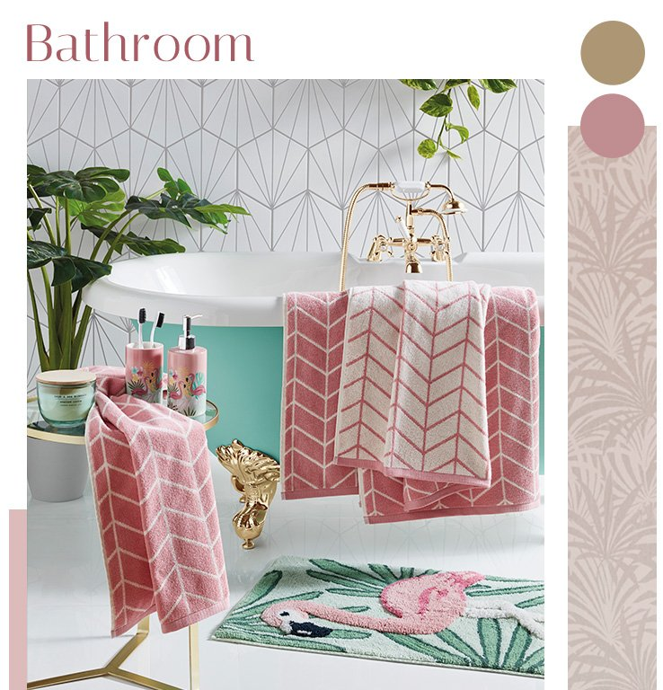 A bath with pink patterned towels, a flamingo rug and a side table with tumblers and another towel