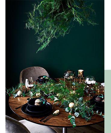 Wooden table decorated with black dinnerware, iridescent wine glasses, leaves and fairy lights
