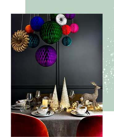 Dining table decorated with a stag ornament, Christmas tree ornaments, dinnerware, candles and fairy lights