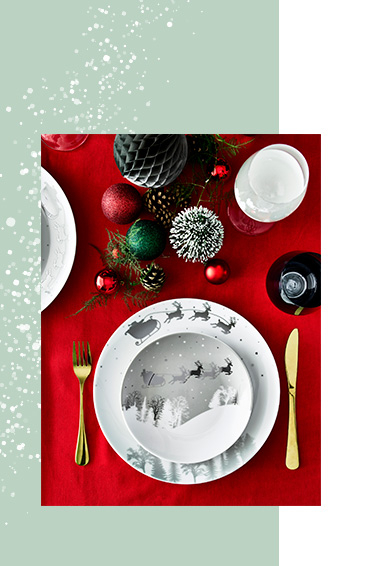 Birds eye view of a festive side plate stacked on top of a co-ordinating dinner plate with a gold effect fork and knife