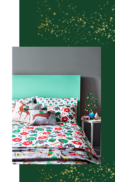Bed dressed in a duvet set designed with christmas jumpers, co-ordinating festive cushions and a throw