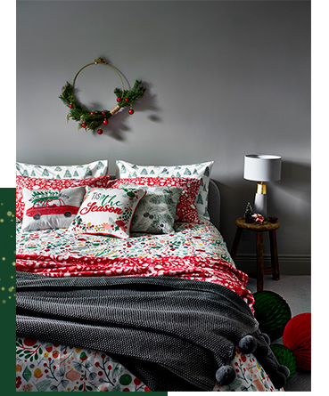 Bed dressed in a festive duvet set, grey pom pom throw and co-ordinating cushions and pillows