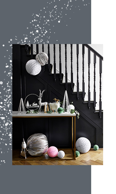 Black staircase with a table in front decorated with Christmas ornaments and origami baubles