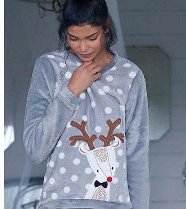 A woman wears a reindeer pyjama top.